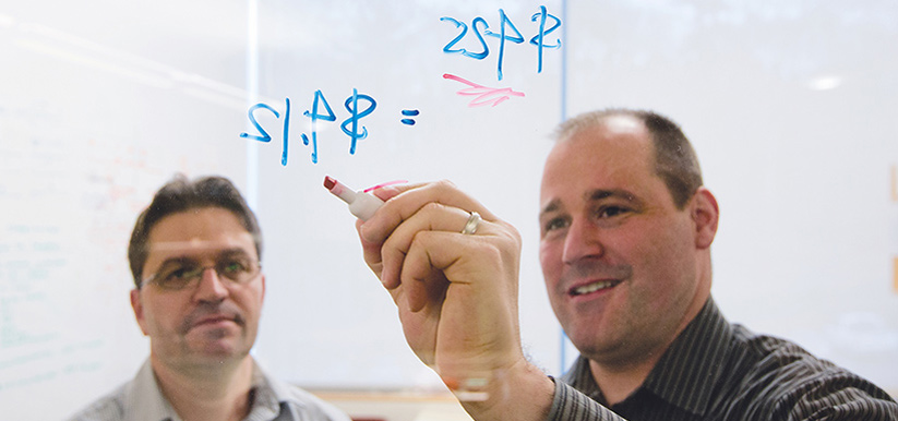 Two men making calculations on a glass window