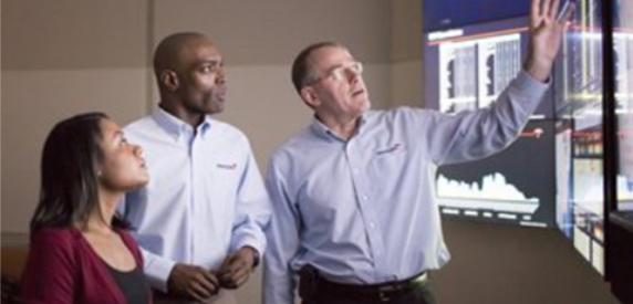 3 employees looking at a screen
