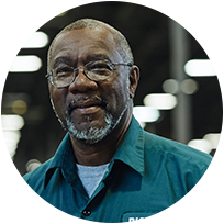 Man smiling wearing glasses and green collared shirt in Dick's Sporting Goods distribution center.
