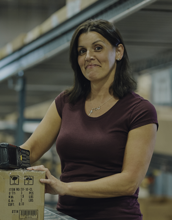 Woman wearing short-sleeved shirt with a brown package in distribution center