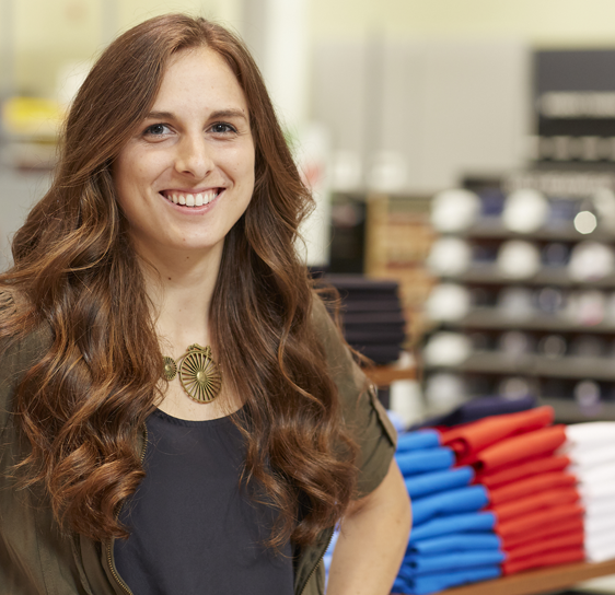 Woman in blue blouse smiling in Dick's Sporting Goods retail store clothing department.
