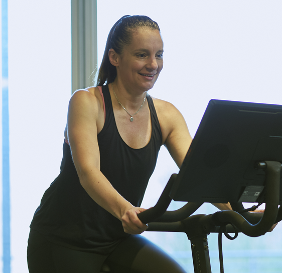 Woman in black tank and pants working out on a stationary bicycle.