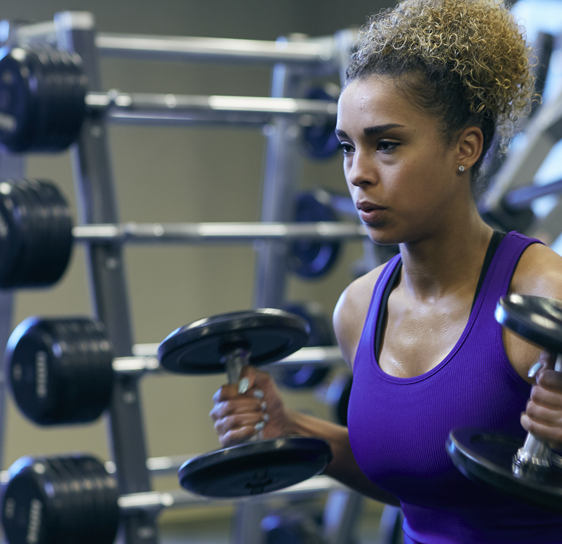 Woman in blue tank lifting weighted dumbbells.