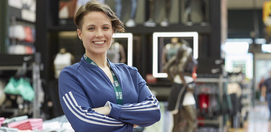 a29d4e8e002 Woman smiling wearing blue long-sleeved shirt in Dick's Sporting Goods  retail store.
