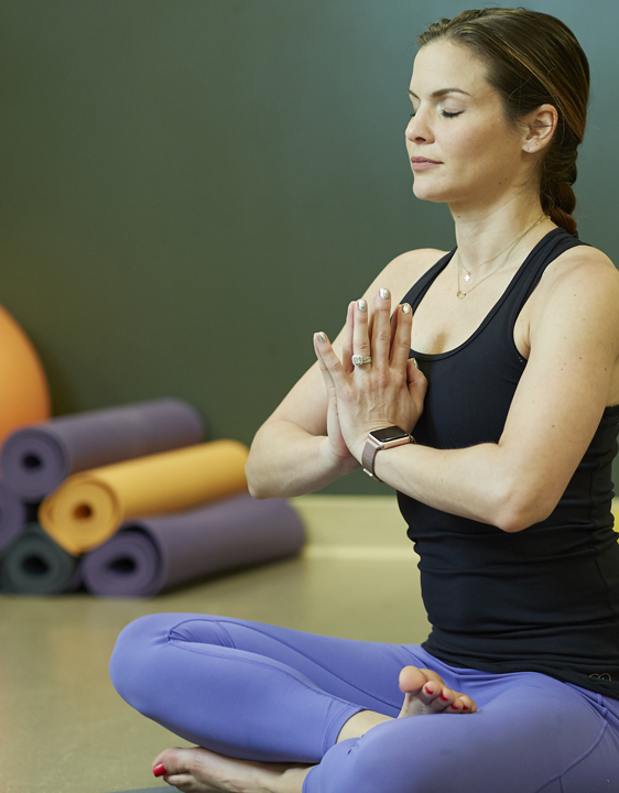 Woman wearing blank tank and purple pants in resting yoga pose. She has her hands placed in front of her chest in half lotus pose. In the background are a set of 6 yoga mats, rolled up and stacked in a triangle. The mats vary in colors of purple, yellow and black.