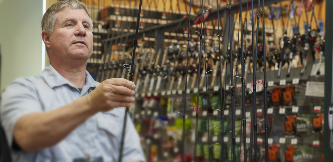 Man wearing white collared short-sleeve shirt holding a fishing pole in a Field & Stream fishing department.