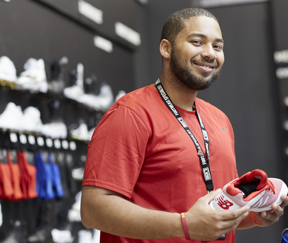 Man wearing red t-shirt holding athletic shoe in Dick's Sporting Goods shoe department. In the background is mixed merchandise including shoes in black & white, and socks in various colors of red and blue).
