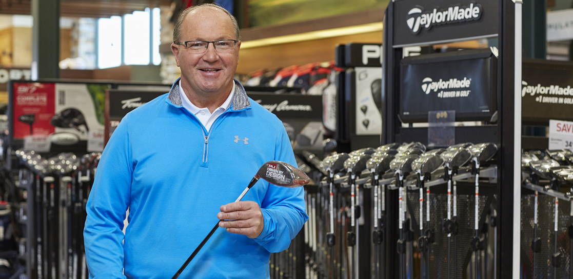 Man wearing white polo with blue pullover jacket holding a golfing iron club in a Golf Galaxy retail department.