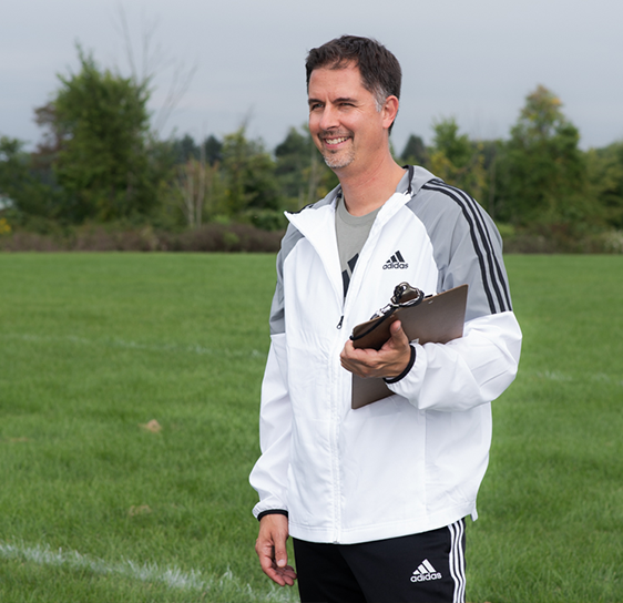 Man standing in an open soccer field. He is wearing a white Adidas jacket and black Adidas pants. He is holding a clipboard in his left arm and smiling at his team off of the camera.