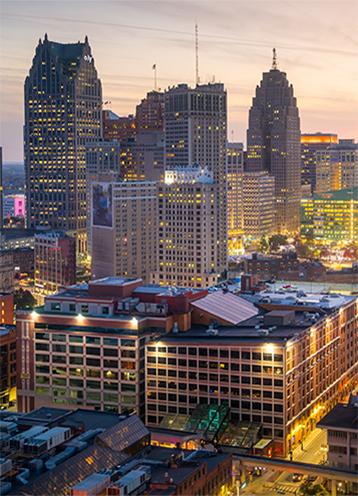 Paisagem urbana no centro de Detroit ao entardecer com luzes acesas nos edifícios