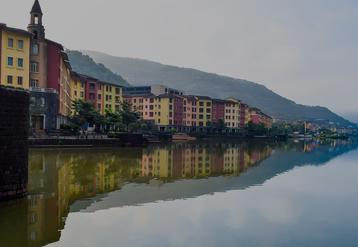 Fila variopinta di costruzioni che si riflettono sulle tranquille acque di un fiume