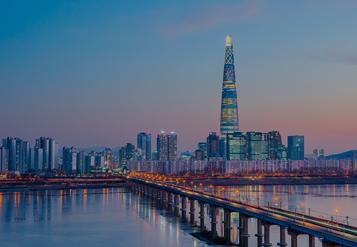 El paisaje urbano de Seúl se refleja en un cuerpo de agua al anochecer