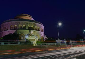Vivekananda House em uma estrada calma com as luzes refletindo no prédio.