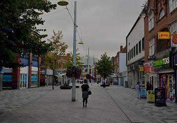 Calle de un vecindario con muchas tiendas y árboles.