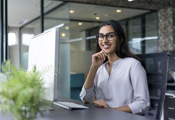 Una joven sentada frente a un escritorio en una oficina.