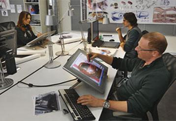 Empregados sentados em uma mesa grande trabalhando em computadores.