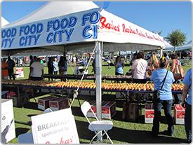 Línea de fruta fresca en una mesa debajo de una carpa blanca de Food City en un evento al aire libre de la comunidad local. La gente camina cerca de la carpa.