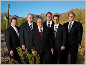 Vestidos con trajes negros, el equipo de liderazgo de Bashas' se para sonriendo en frente a pequeñas montañas y cactus.