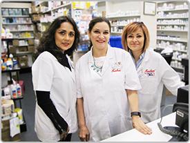 Tres farmacéuticas están sonriendo juntas detrás de un mostrador de farmacia.