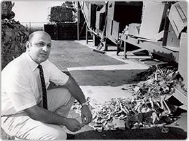 Un empleado histórico de Bashas' se agacha frente a una pila de cartón para reciclar.