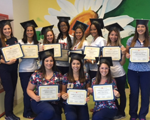 Group of nurses in graduation caps holding their certificates