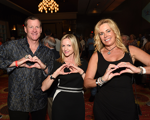 A man and two women forming a heart symbol with their hands