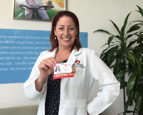 Nurse in white lab coat holding her name badge
