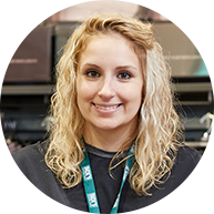Woman smiling wearing blue long-sleeved shirt in Dick's Sporting Goods retail store.