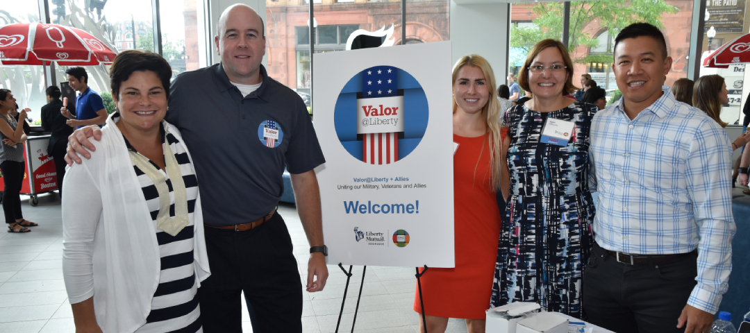 group of liberty mutual employees standing next to a valor at liberty poster