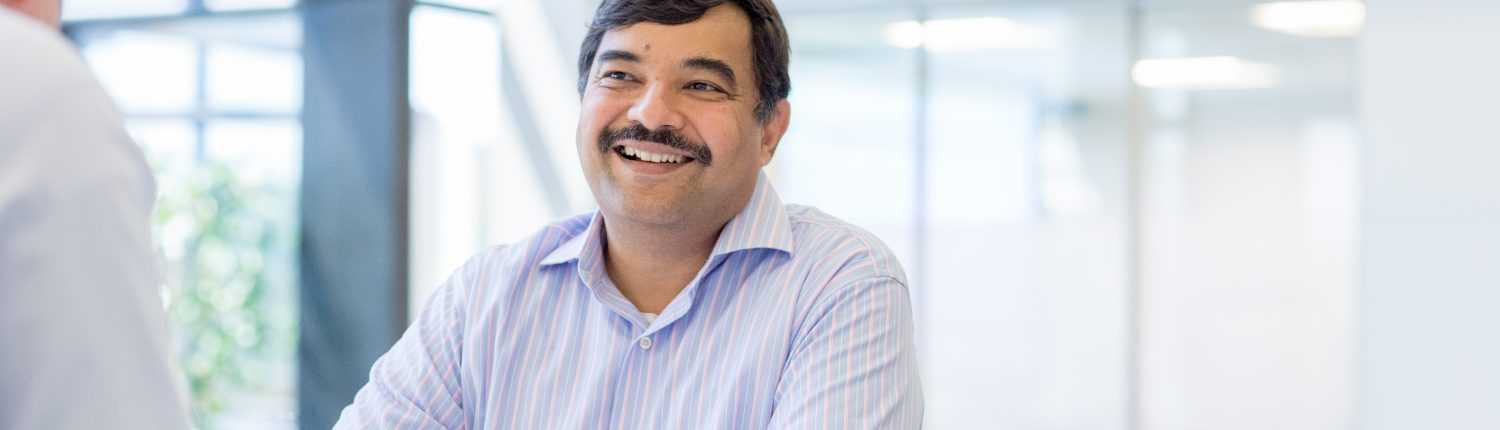 man with moustache smiling with hands clasped