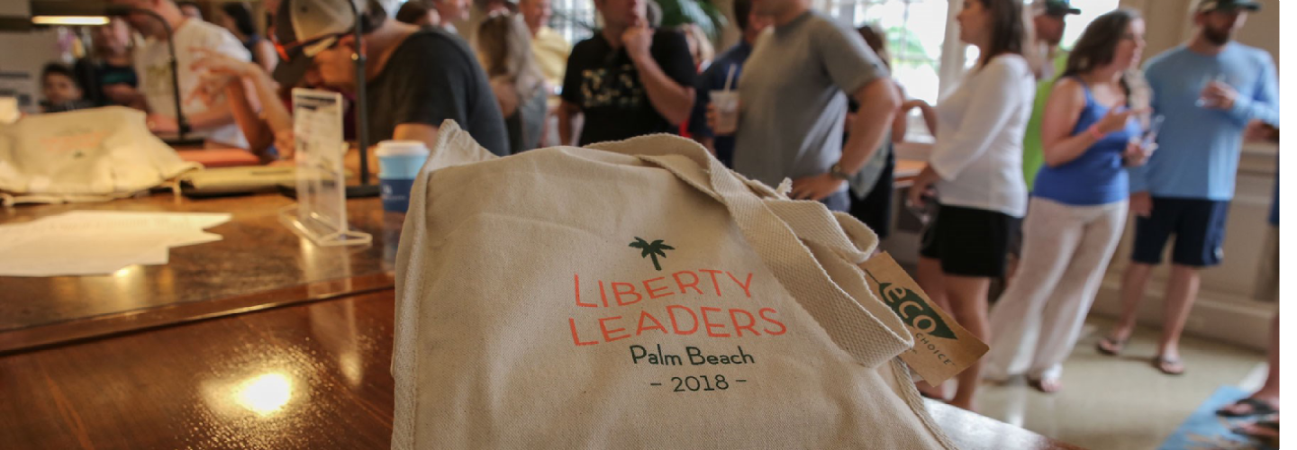 liberty leaders canvas tote bag in foreground; people socializing at background