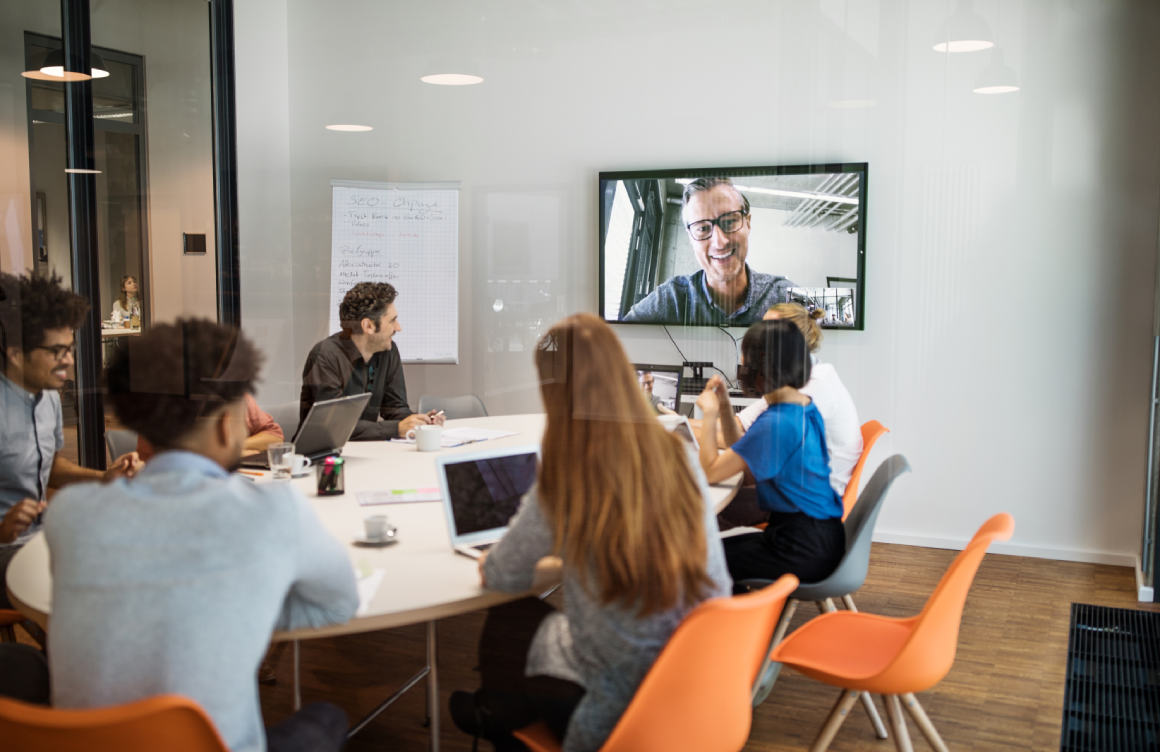 group of people sitting in conference room looking at the video conference screen