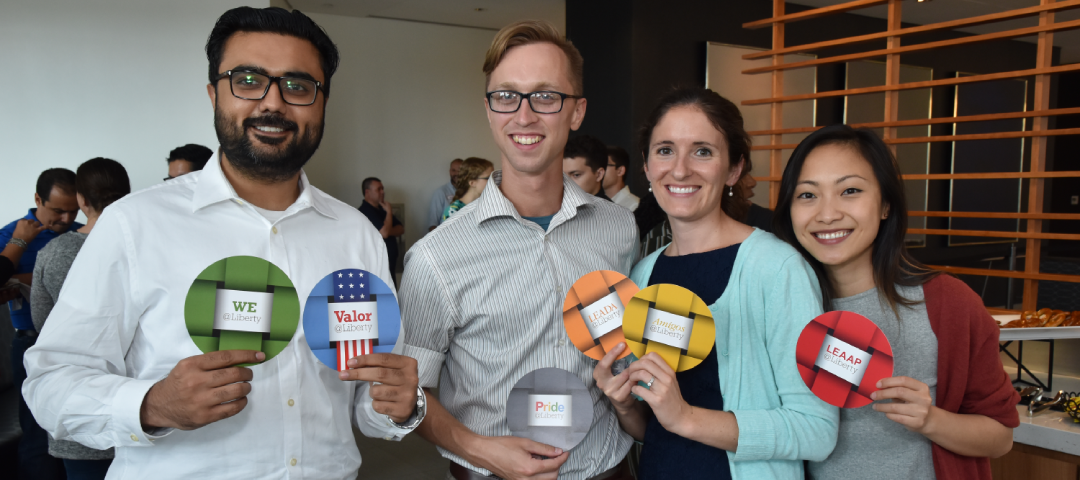 group of liberty mutual employees smiling while holding up employee resource group badges