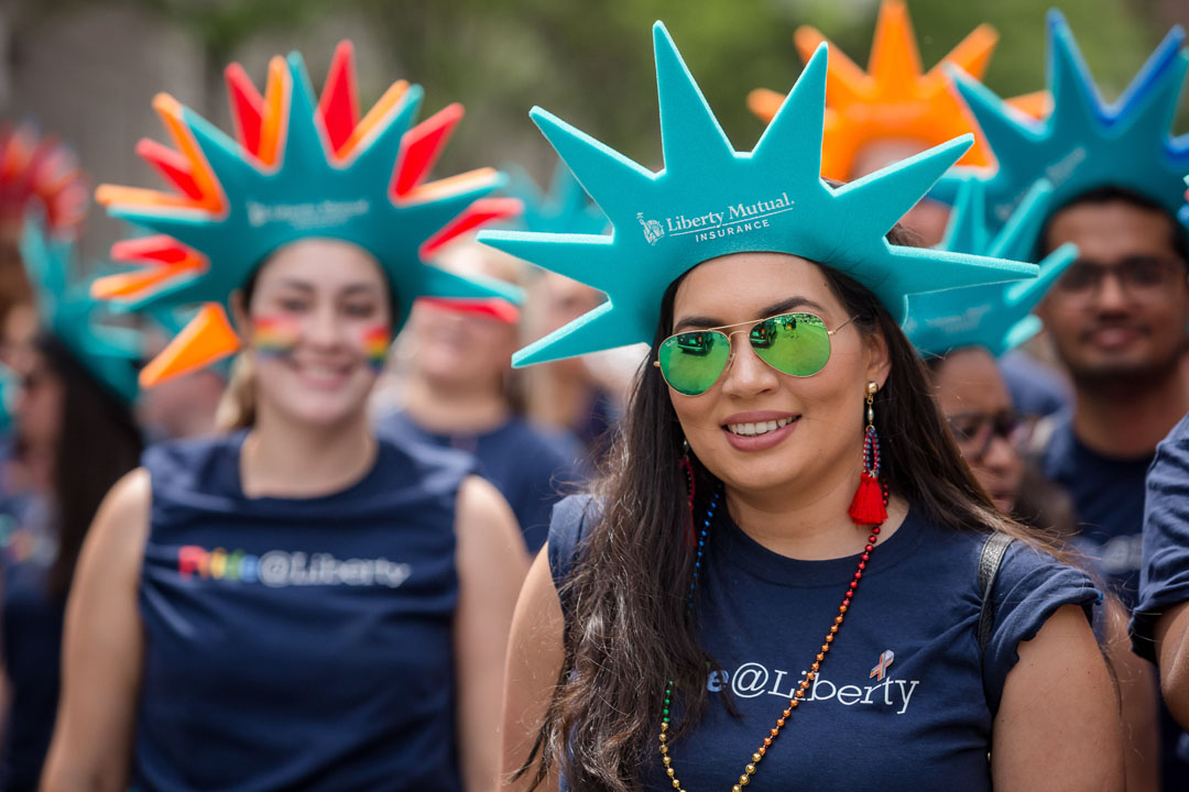 female liberty mutual employee wearing lady liberty hat at pride parade in foreground; people wearing lady liberty hats in background