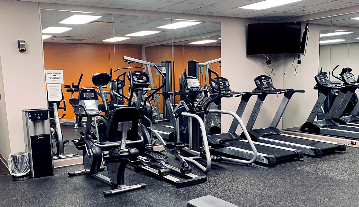 treadmills, elliptical and television inside fitness center