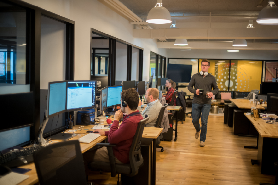 man walking at solaria labs office while people sit and work at desks