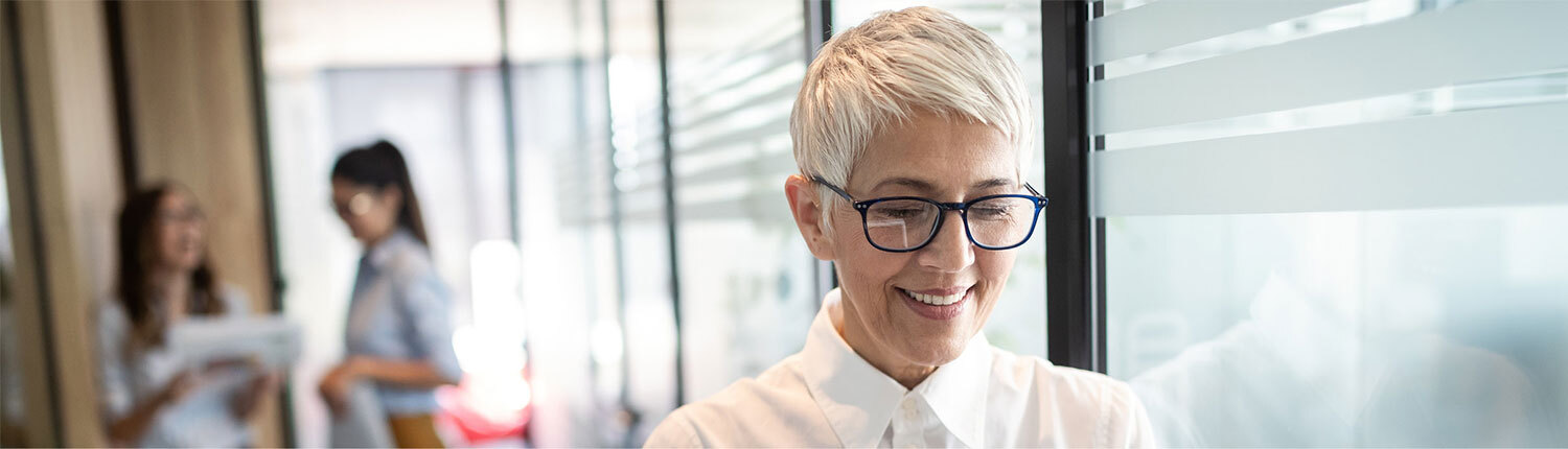 Middle-age woman with short white hair wearing glasses, reading content off screen