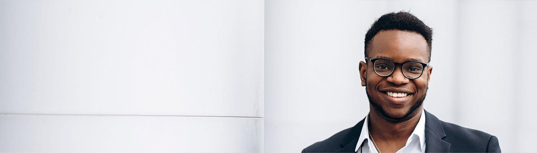 Professional black man wearing glasses smiling to camera