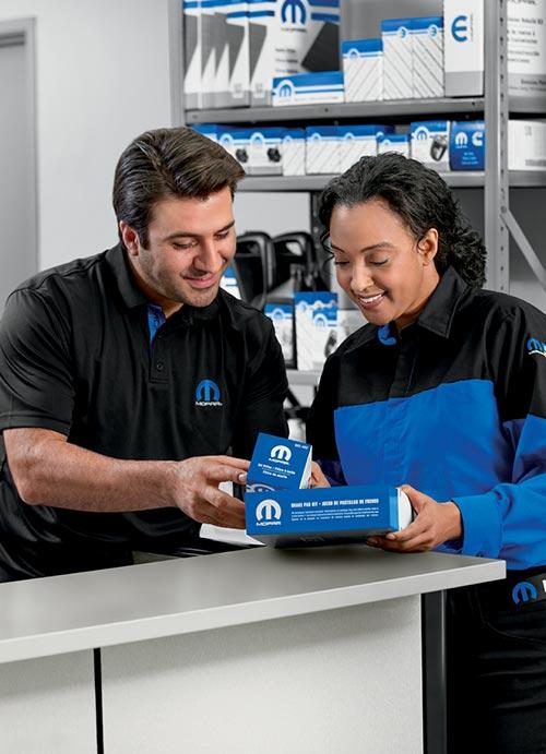 Mopar® 애프터마켓 부품을 보는 두 직원.