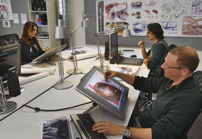 큰 테이블 주위에 앉아 컴퓨터로 일하는 직원들.