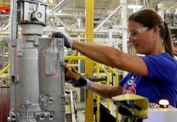 보안경을 착용한 상태로 제조 시설에서 일하는 여성.