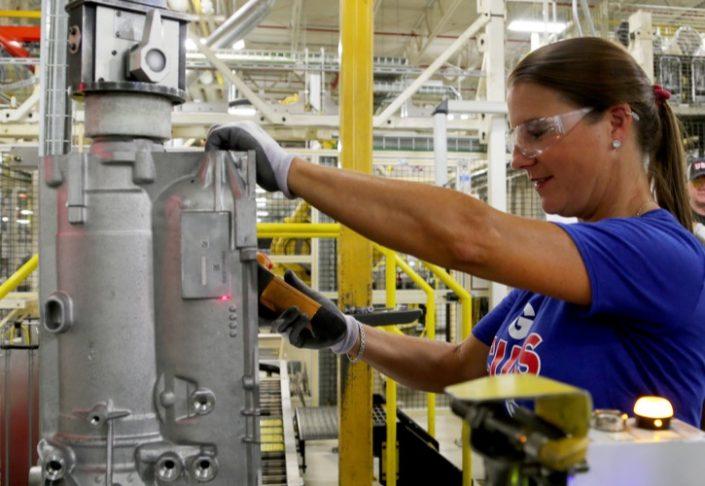 보호경을 착용한 상태로 제조 시설에서 일하는 여성.