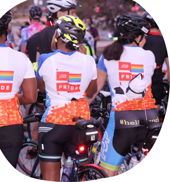 three ADP associates on bicycles wearing ADP Pride cycling shirts