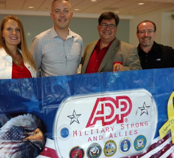 four ADP associates standing behind a banner that reads 'ADP Military Strong and Allies