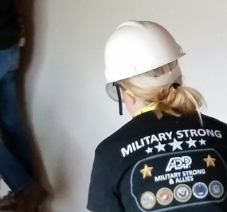 ADP associate wearing black 'Military Strong' T-shirt and white construction hardhat