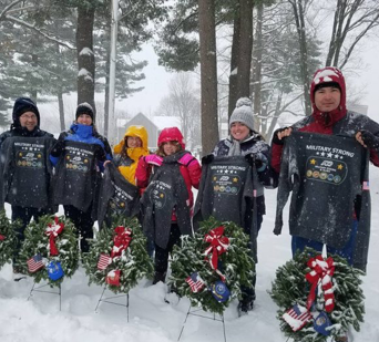 "A group of ADP associates holding ""Military Strong"" sweatshirts and standing behind holiday wreaths"