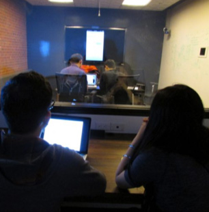 two ADP associates observing a group of people in another room through a window
