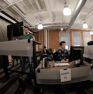 Two ADP associates: one using a standing desk; another seated at another desk