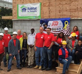 group of ADP associates in red ADP T-shirts and construction hardhats