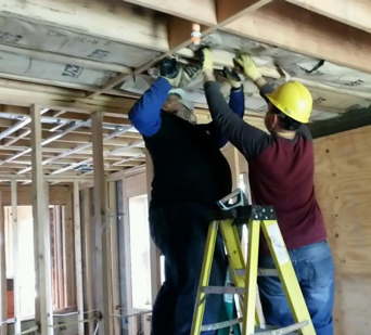 two ADP associates on a ladder and wearing construction hardhats